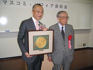コムソフィア賞の刻字を持つ山田五郎さん(左)と濱口浩三会長